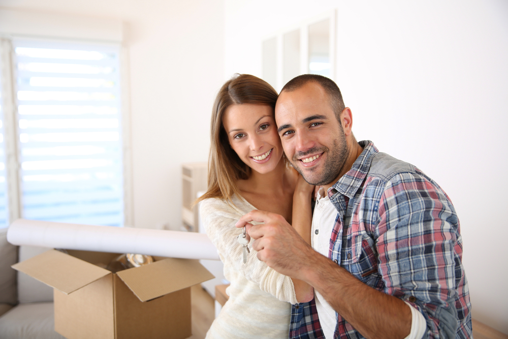 A smiling man and woman in a house with cardboard boxes