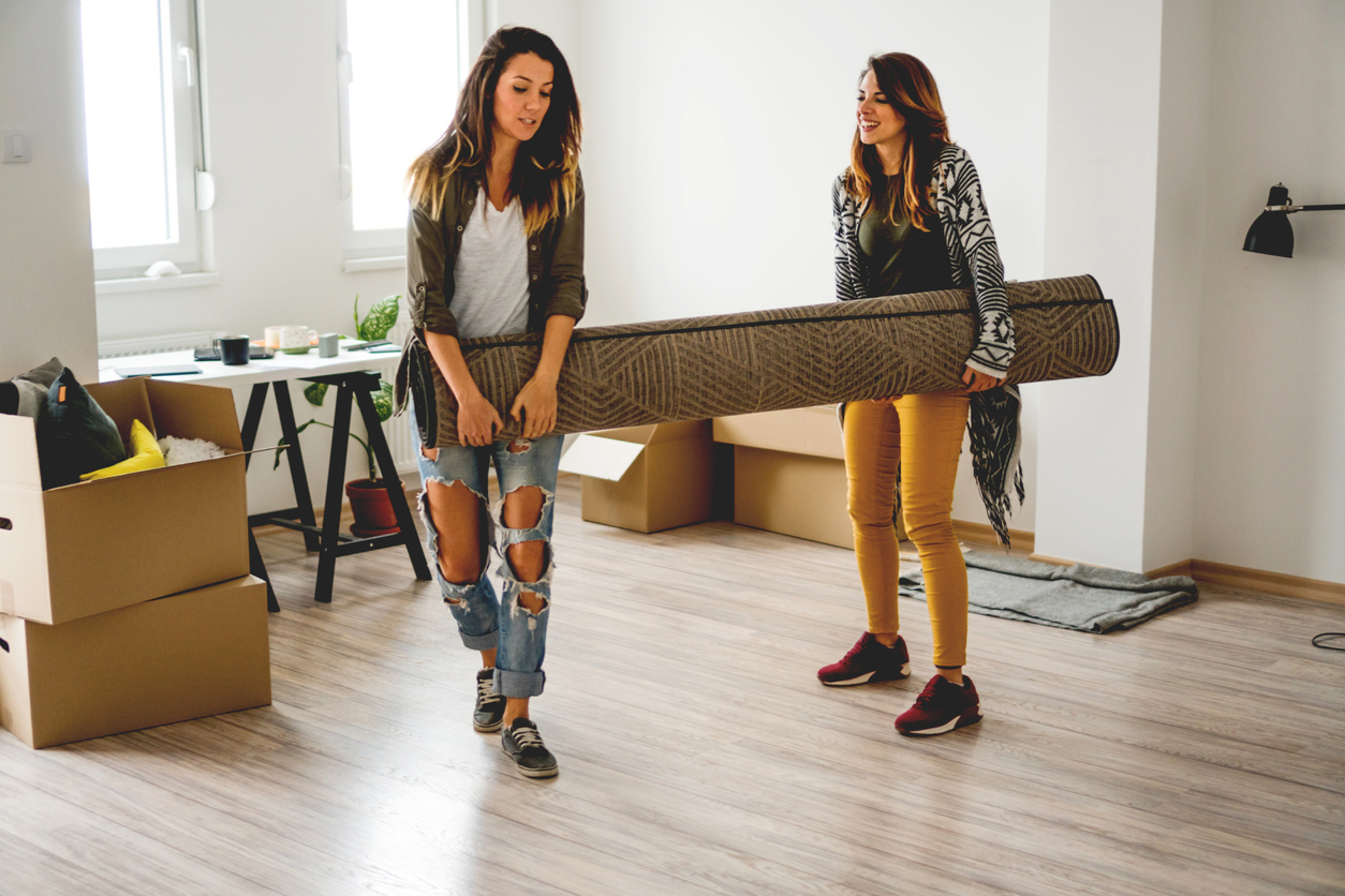 Couple carrying carpet in new home